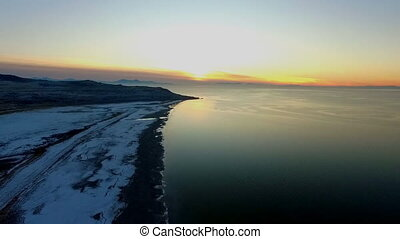 Aerial view of a stunning sunset on the horizon of a beach shore or coastline of a large lake, sea or ocean