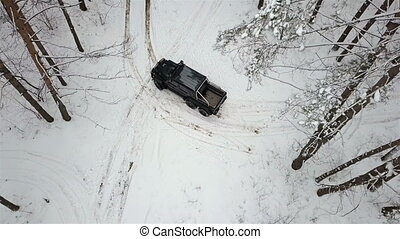 Aerial view of a SUV 6x6, standing on the snow-covered road in winter forest