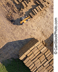 Aerial view of a tractor folding bales of hay in a field on...