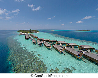 Aerial view of a tropical island in turquoise water. Luxurious over-water villas on tropical island resort maldives for holiday vacation background concept -Boost up color Processing.