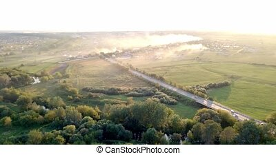 Aerial view of a truck and other traffic driving along a road at sunrise. Beautiful sunset over the road full of traffic and long river. Great skies. Beautiful autumn. Colorful nature