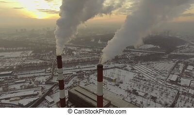 Aerial view of a tube with smoke at winter sunset