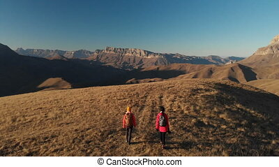 Aerial view of a two girls traveler with backpacks and cameras stroll through the hills between the epic rocks in the mountains. Girls photographers with their cameras at sunset