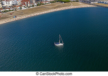 aerial view of a white sailboat in front of a sandy beach