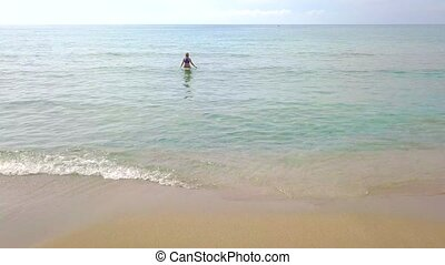Aerial view of a woman comes out of the clear sea. Summer...