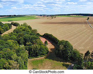 Aerial view of agriculture farmland and and small house during dry summer season