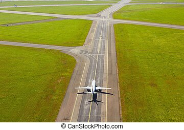 Aerial view of airport - airplane is taxiing to take off