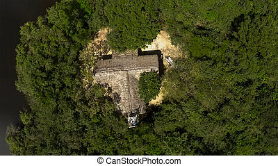 aerial view of alone hut in the middle of a jungle rain forest on a tropical island