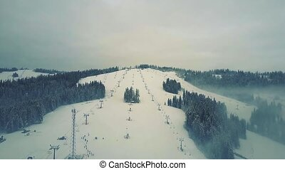 Aerial view of alpine skiing slopes and ski lifts in winter....