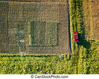 Aerial view of amid fields with red car on it - Aerial drone...