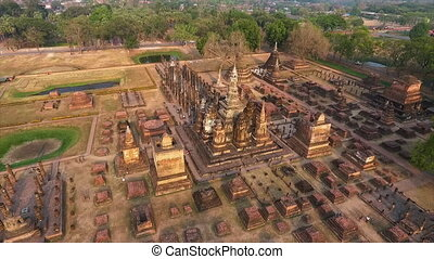 An aerial shot of an ancient stupa close to a small water body in a park in an ancient temple in Sukhothai, Thailand