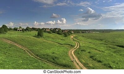 Aerial view of an unknown girl riding her bike along the field road on a summer day