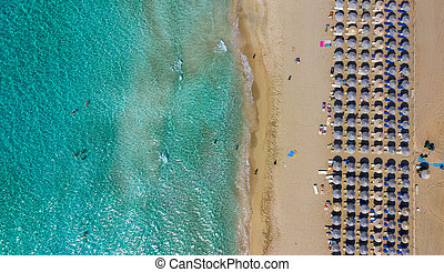 Aerial view of aTop down aerial view of amazing beach with umbrellas and turquoise sea at sunset. Mediterranean sea, Crete, Greece. mazing beach with umbrellas and turquoise sea at sunset. Mediterranean sea, Crete, Greece.