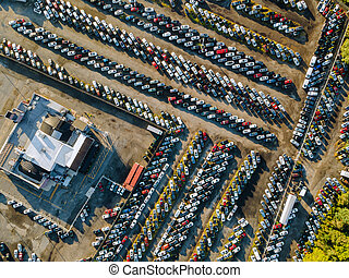 Aerial view of auto auction many used car lot parked distributed in a parking.