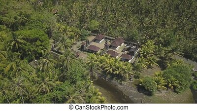 Aerial view of Balinese temple in palm forest