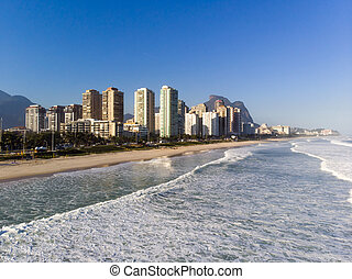 Aerial view of Barra da Tijuca beach during late afternoon with foamy waves. Rio de Janeiro, Brazil.