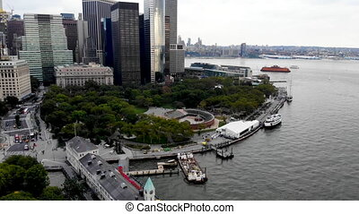 Aerial view of Battery Park pier A leading to Liberty Island, people can be seen waiting in line for boarding as well as looking at Liberty Island located opposite to the docks. October, 22nd, 2019