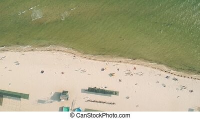 Aerial view of beach shore with swimming people.