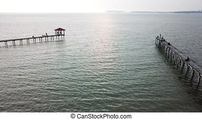 Aerial view of beautiful beach and old jetty during sunset.