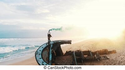 Aerial view of beautiful girl with colored smoke at the beach