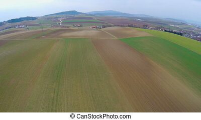 """Aerial view of beautiful green landscape with cultivated fields and farmland"""