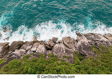 Aerial view of beautiful ocean waves and rocky coast with greenery