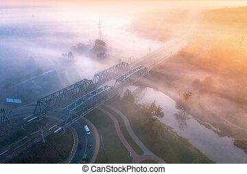 Aerial view of beautiful railroad bridge and river in fog in fall
