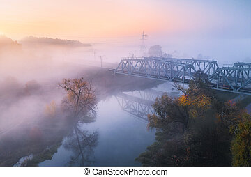 Aerial view of beautiful railroad bridge and river in fog in fall