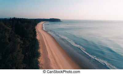 Aerial view of beautiful sandy beach and sea during sunset