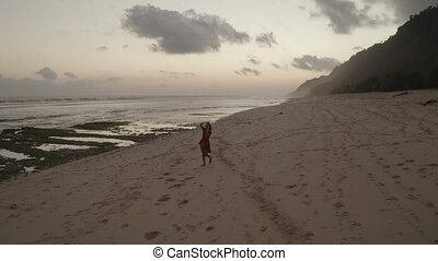 Aerial view of beautiful woman in red dress on the beach at sunset