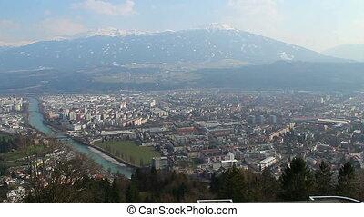 Aerial view of big city, river, Austrian Alps, mountain ridge