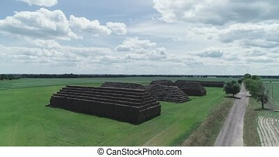 Aerial view of big pyramids made out of rectangular haystacks.