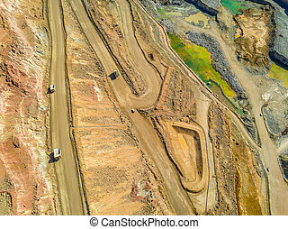 Aerial view of big trucks in huge, open pit mine
