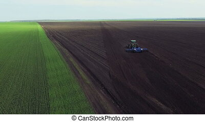 Aerial view of black fertile soil, tractor plowing the soil