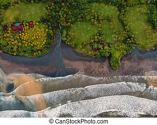 Aerial view of black sand beach with ocean and waves in Balian, Bali