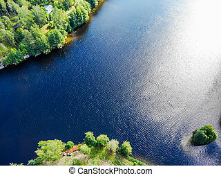 Aerial view of blue lake and green forest on a sunny summer day in Finland. Drone photography