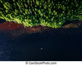 Aerial view of blue lake with a fishing boat and green woods on a sunny summer day in Finland.