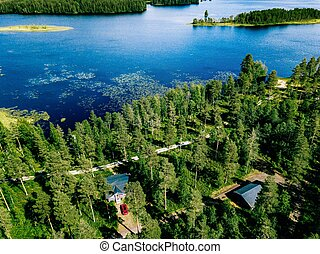 Aerial view of blue lake with green forests in Finland. Wooden house, sauna, boats and fishing pier by the lake.