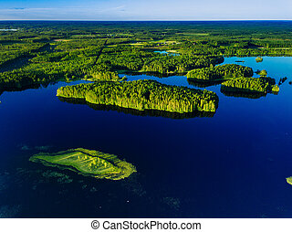 Aerial view of blue lakes and green forests on a sunny summer day in Finland.