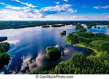 Aerial view of blue lakes and green forests on a sunny summer day in Finland from above