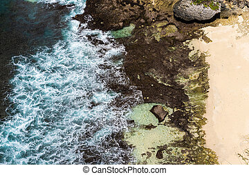 Aerial view of blue ocean waves crashing into rocky coast