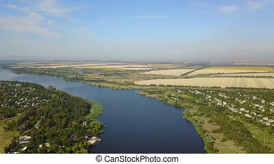 Aerial View Of Blue River With Small Village And Fields On Banks, Drone Shot Of Rural Summer Landscape