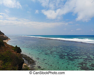 Aerial view of blue transparent ocean over sandy coastline with cliff, Bali