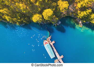Aerial view of boats, wooden jetty in blue see and green trees