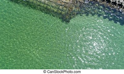 aerial view of breakwater of concrete in the ocean