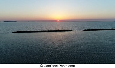 aerial view of breakwater of stone at sunset