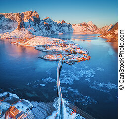 Aerial view of bridge over the sea and snowy mountains in Norway