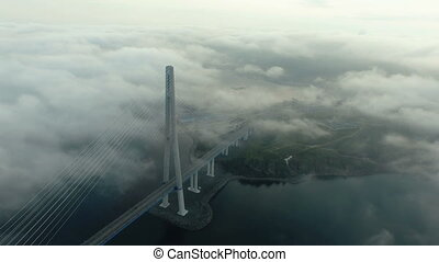 Aerial view of Bridge Russky through the Strait of Eastern Bosphorus abve the clouds