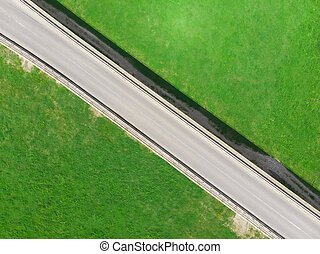 aerial view of bridge with road in the green grass