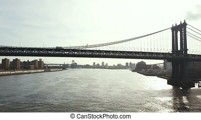 Aerial view of Brooklyn bridge through the East river in New York, America. Drone flying under the road on the bridge